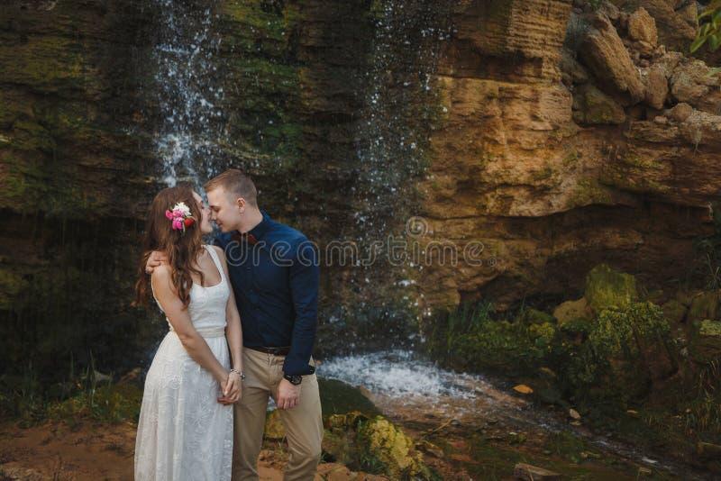 De openluchthuwelijksceremonie, de modieuze gelukkige glimlachende bruidegom en de bruid koesteren en kussen voor kleine waterval stock foto's