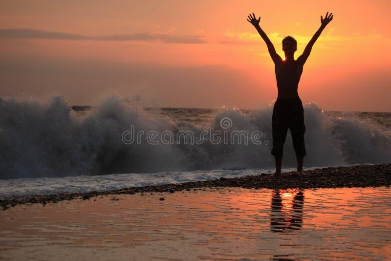 De opgeheven handen van het silhouet kerel naar omhoog op zonsondergang stock afbeelding