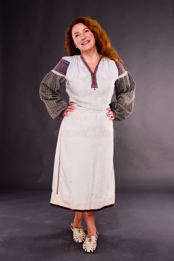 De opgetogen vrouw van het land in vlaskleding met borduurwerk stock fotografie