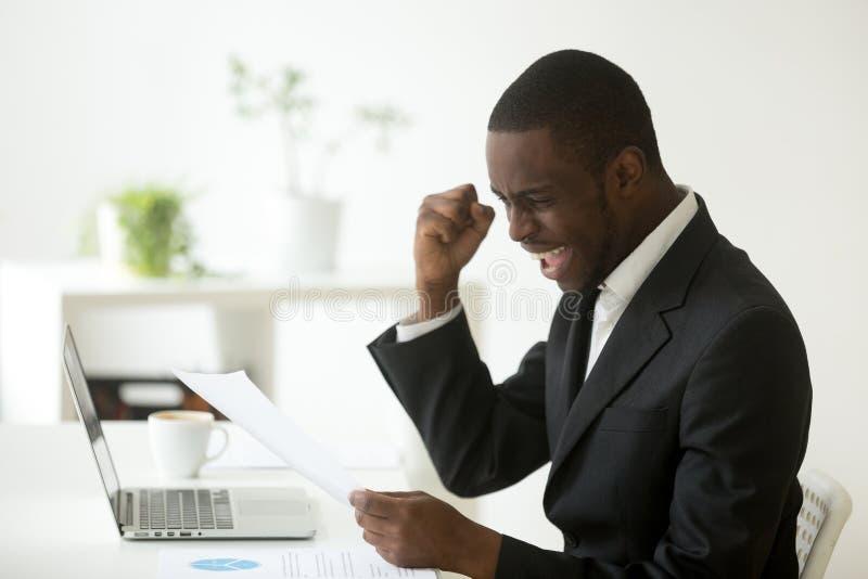 De opgewekte Afrikaanse Amerikaanse brief van de zakenmanlezing met unexpec royalty-vrije stock fotografie