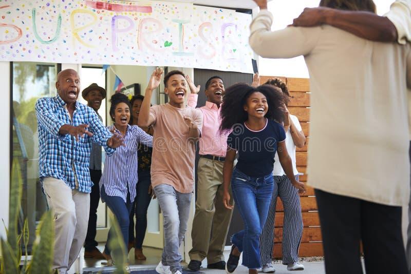 De opgewekte Afrikaanse Amerikaanse familie welkom hetende gasten bij een partij van het verrassingshuis, sluiten omhoog royalty-vrije stock foto's
