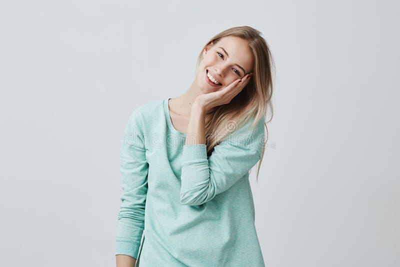 De opgewekte extatische mooie blondevrouw houdt hand op wang, glimlacht met plezier zoals opmerkt prettig iets royalty-vrije stock foto's