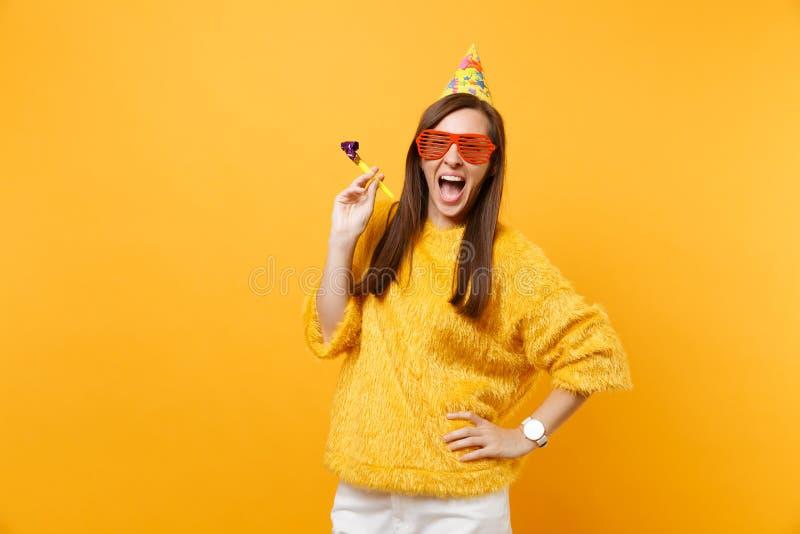 De opgewekte gelukkige jonge vrouw in oranje grappige de partijhoed van de oogglazenverjaardag met het spelen van pijp het vieren royalty-vrije stock fotografie