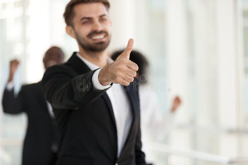 De opgewekte glimlachende werknemer, manager toont duimen omhoog dichte omhooggaand royalty-vrije stock fotografie