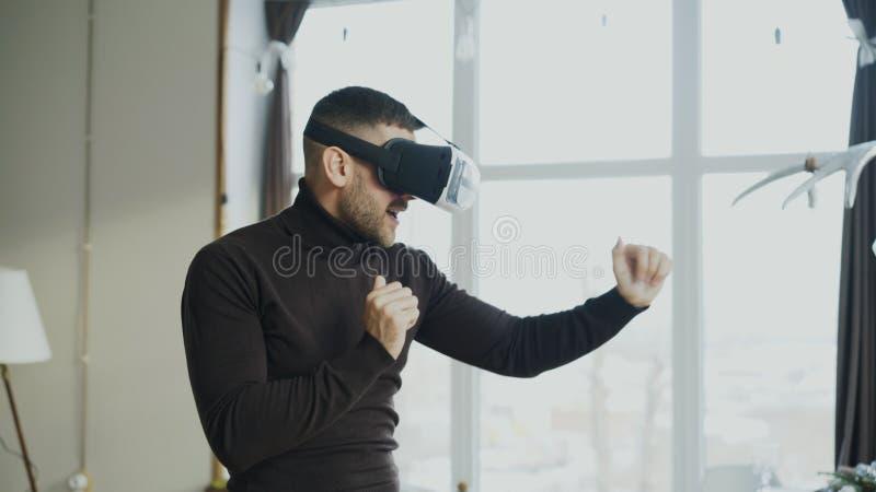 De opgewekte jonge mens met virtuele werkelijkheidshoofdtelefoon die en speelt thuis videospelletje 360 dansen royalty-vrije stock afbeeldingen