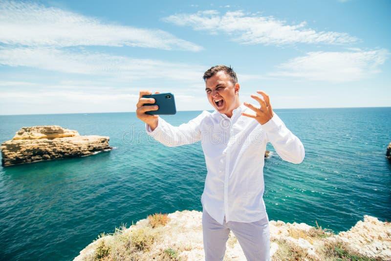 De opgewekte jonge mens neemt foto van zich op mobiele telefoon Hij bevindt zich op klip dichtbij het overzees en de schreeuw stock afbeeldingen