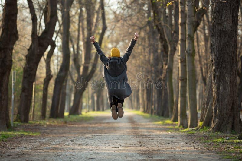 De opgewekte jonge vrouw springt met omhoog opgeheven wapens royalty-vrije stock afbeelding