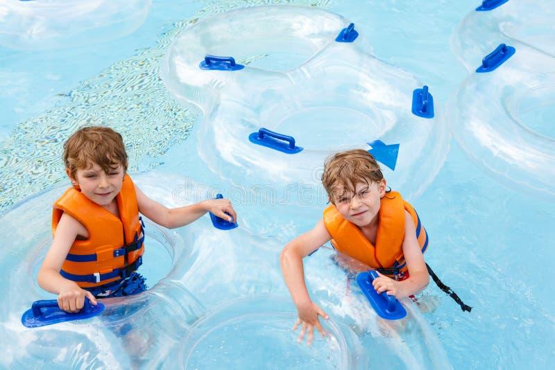 De opgewekte kinderen in water parkeren het berijden op dia met vlotter stock afbeelding
