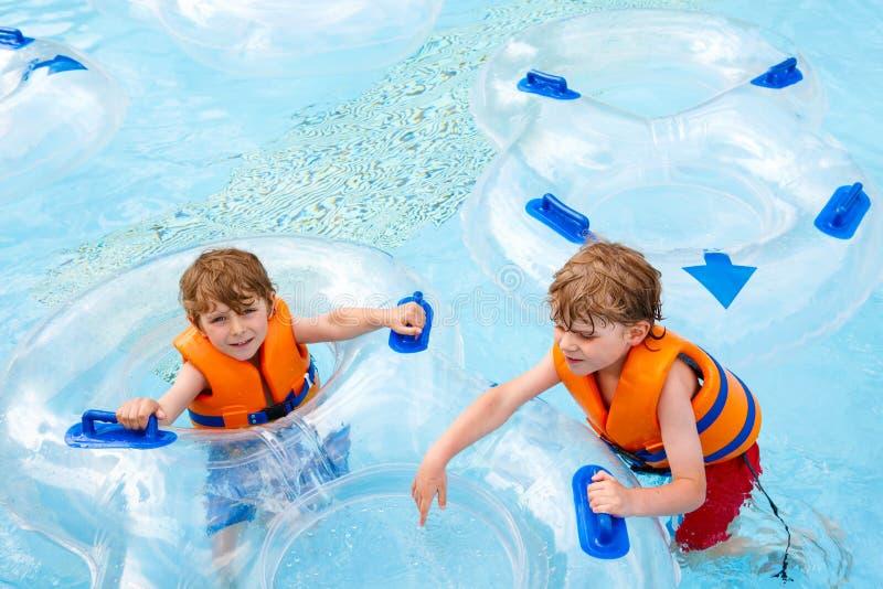 De opgewekte kinderen in water parkeren het berijden op dia met vlotter royalty-vrije stock afbeelding