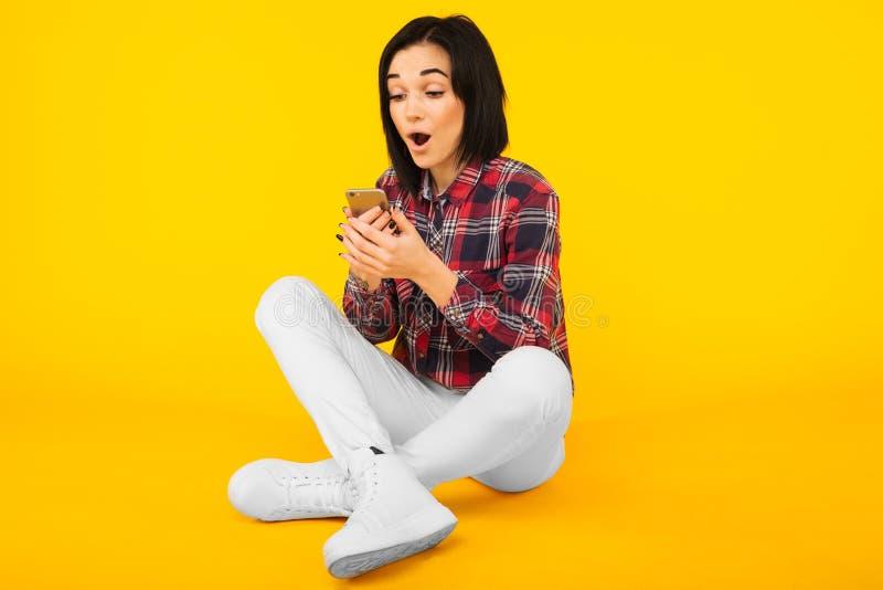 De opgewekte lachende vrouw in plaidoverhemd zit en gebruikend mobiele telefoon over gele achtergrond stock fotografie
