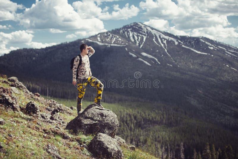 De opgewekte mens die op een bergbovenkant wandelen met rugzak geniet van de mening en het zoeken van avonturen stock foto