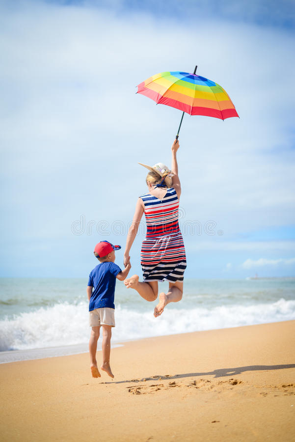 De opgewekte moederzoon heeft in openlucht pretsprong op zonnige strandachtergrond royalty-vrije stock afbeelding