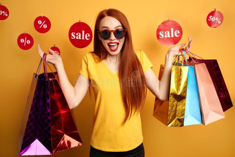 De opgewekte winkelende vrouw in zonnebril drukt vreugde uit stock afbeelding