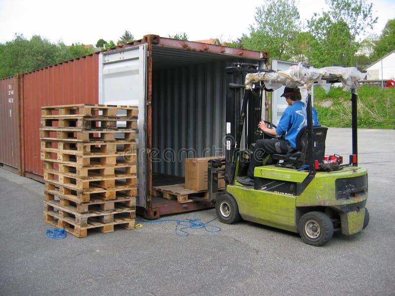 De opheffende pallet van de vrachtwagen uit container stock fotografie