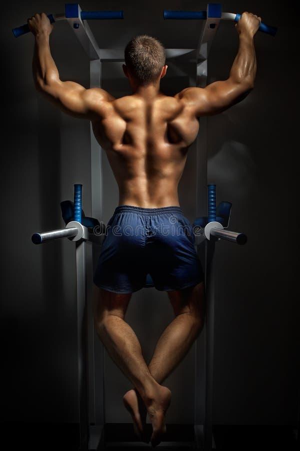 De opleiding van de bodybuilder in duisternis stock fotografie