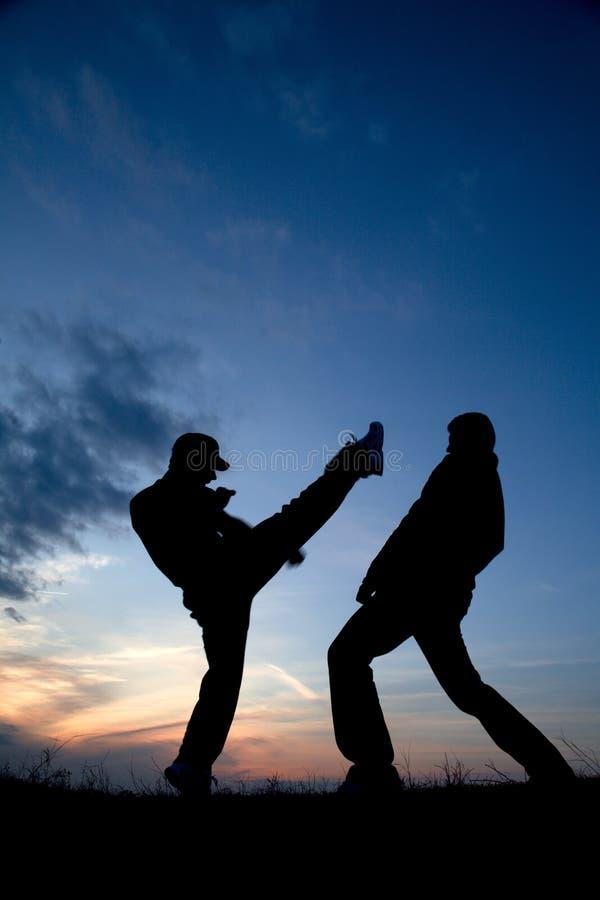 De opleiding van de karate door zonsondergang stock afbeelding