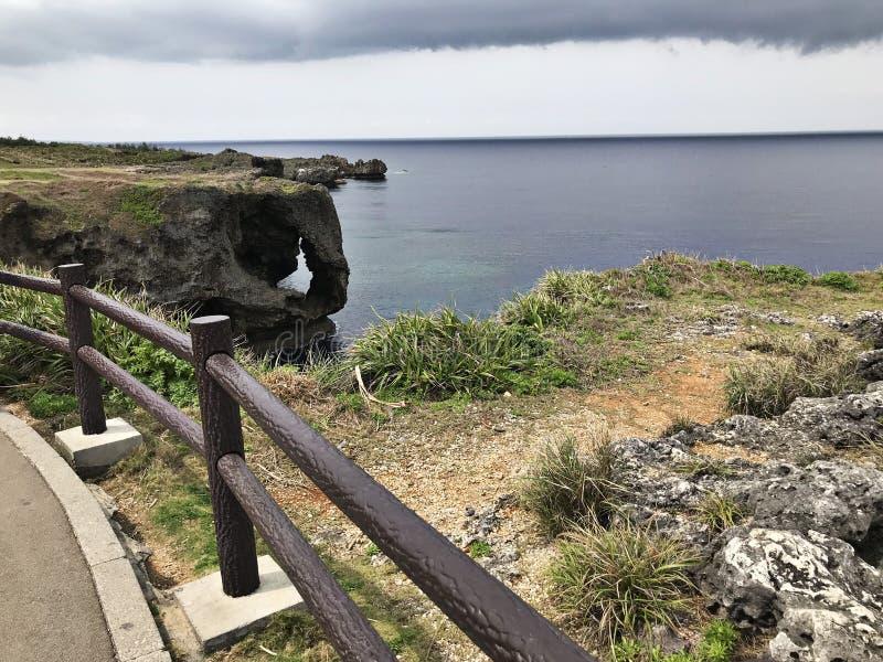De opmerkelijke klip en een verblindende mening van smaragdgroene oceaan bij Kaap Manzamo in Japan royalty-vrije stock foto