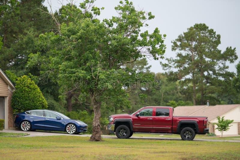 De oprijlaan met Tesla Model 3 elektrische opgeheven auto en rood neemt vrachtwagen op stock fotografie