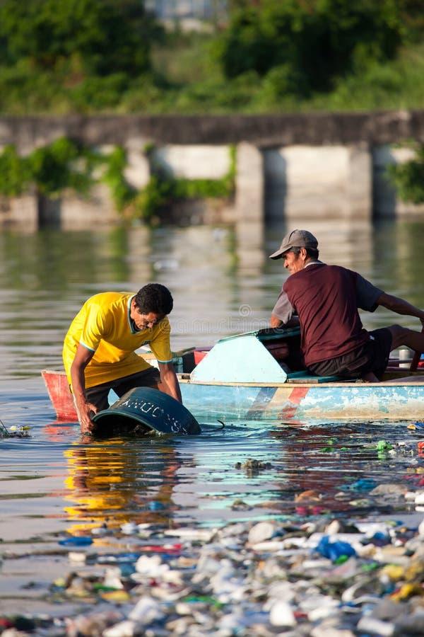 De opruiming van de mens zijn emmer in verontreinigde rivier royalty-vrije stock afbeelding