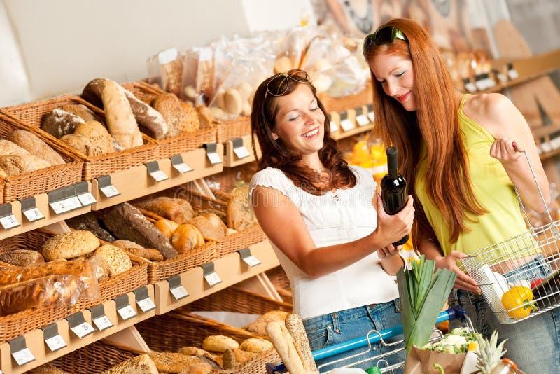 De opslag van de kruidenierswinkel: Twee vrouwen die wijn kiezen royalty-vrije stock afbeeldingen