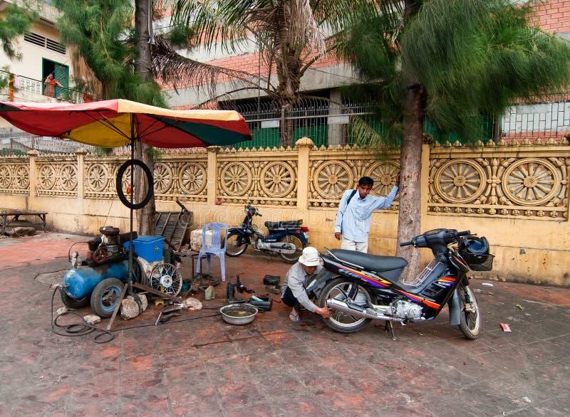 De opstelling van de de motorfietsreparatie van de kant van de weg op een stoep royalty-vrije stock afbeelding