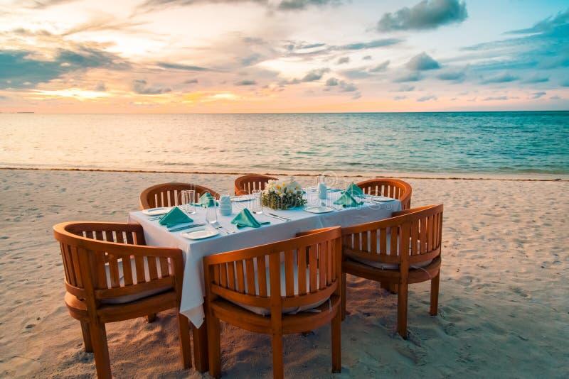 De opstelling van het stranddiner voor paren of honeymooners De scène van het zonsondergangstrand met houten lijst en stoelen kla stock fotografie