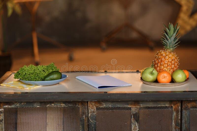 De opstelling van de keukenlijst Leeg notitieboekje en vruchten zijaanzicht stock foto