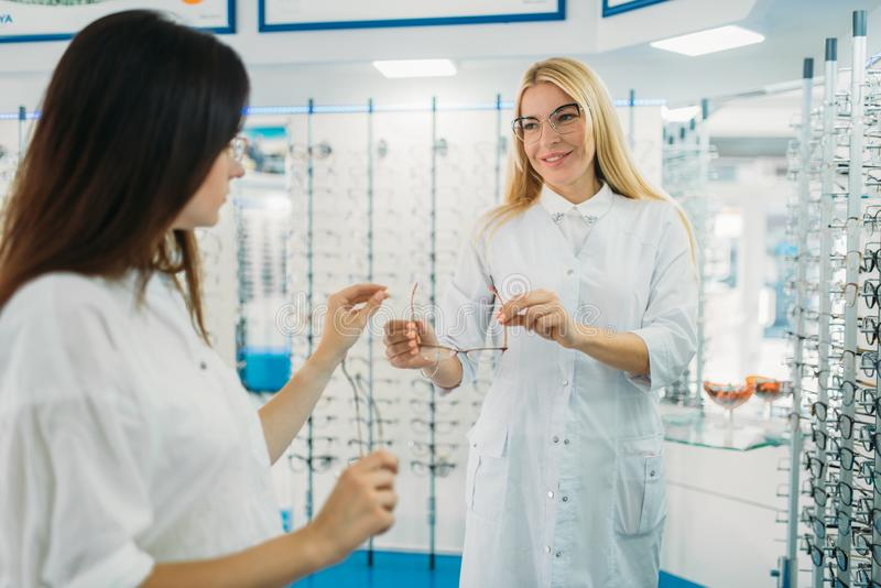De opticien toont glazen aan koper in opticaopslag stock foto's