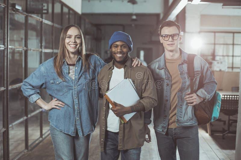 De optimistische gekwalificeerde collega's stellen met glimlach stock foto's