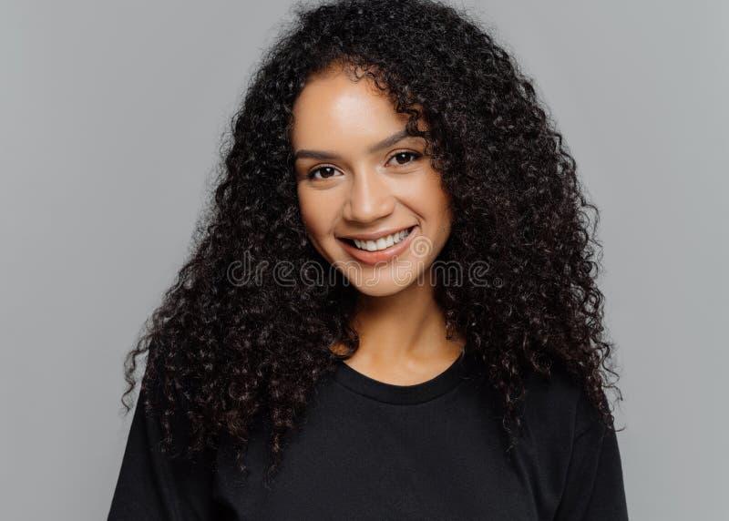 De optimistische krullende jonge vrouw met zachte glimlach, bekijkt positief camera, draagt toevallige zwarte kleren, die op grij royalty-vrije stock afbeeldingen