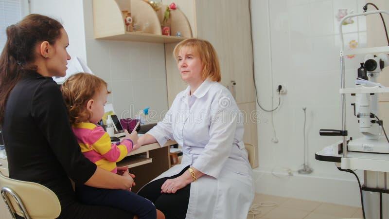 De optometrist controleert kind` s zicht - de moeder en het kind hebben overleg in oftalmoloogruimte royalty-vrije stock fotografie
