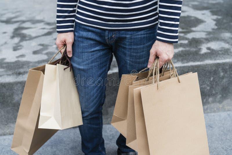 De opwindende jonge het winkelen zakken van de mensengreep stock afbeelding