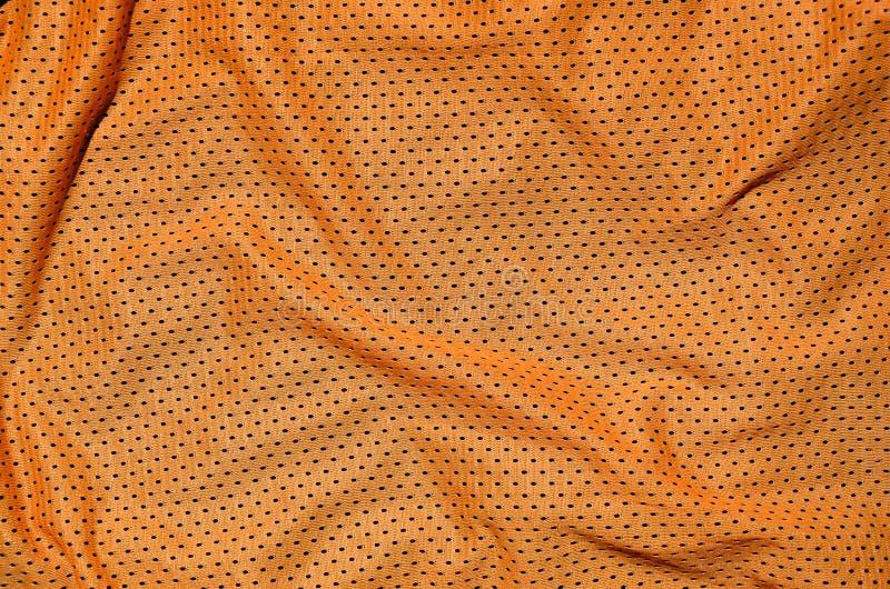 De oranje achtergrond van de de stoffentextuur van de sportkleding Hoogste mening van oranje doek textieloppervlakte Helder baske stock foto's
