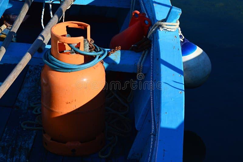 De oranje die gasdruktank als bron van gas voor nacht visserijlamp wordt gebruikt bond aan houten bootbank met roestige ketting royalty-vrije stock fotografie