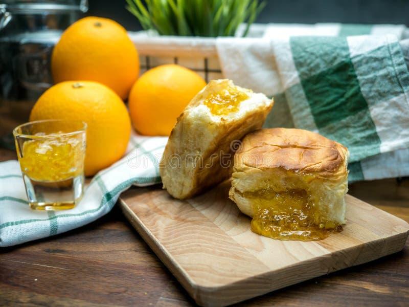 De oranje jam in toostbrood en het oranje fruit op over houten lijst, sinaasappel zijn de achtergrond royalty-vrije stock afbeeldingen