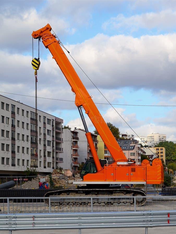 De oranje kruippakjekraan bij de plaats van wegenbouw werkt in de stad tegen de achtergrond van een woningbouw en s stock foto's