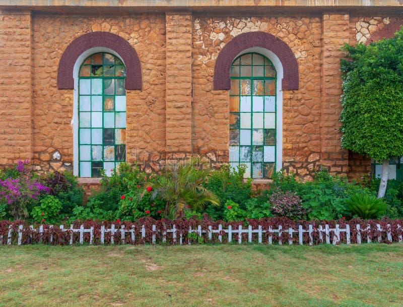 De oranje muur van de bakstenensteen met twee grote oude die grungevensters met groen metaalnet, groene grasvloer, en struiken wo stock afbeeldingen