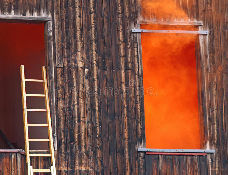 De oranje rook komt uit het venster en uit een ladder van brandne stock foto