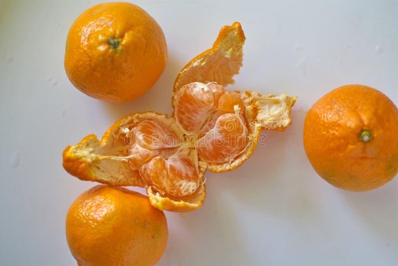 De oranje sinaasappelen liggen op een witte lijst royalty-vrije stock foto