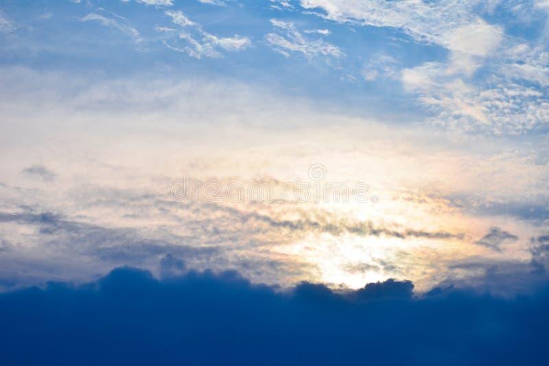 De oranje stralen van de zon maken hun manier door de avondwolken van de blauwe hemel van de blauwe bewolkte hemel stock afbeeldingen
