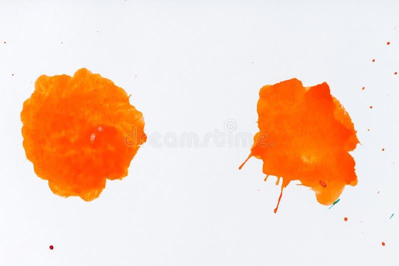 De oranje verf ploetert Verfplonsen op Witte Achtergrond Wate stock foto