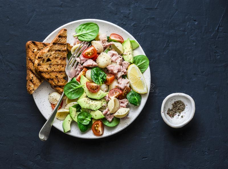 De Orecchiettedeegwaren, de tonijn, de avocado, de spinazie, de tomatensalade en het gehele korrelbrood roosteren - gezonde lunch stock afbeeldingen