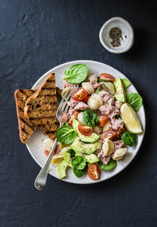 De Orecchiettedeegwaren, de tonijn, de avocado, de spinazie, de tomatensalade en het gehele korrelbrood roosteren - heerlijke gez stock fotografie