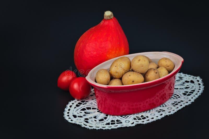 De organische aardappels in rode ceramisch bakken pot, tomaten en pompoen royalty-vrije stock foto