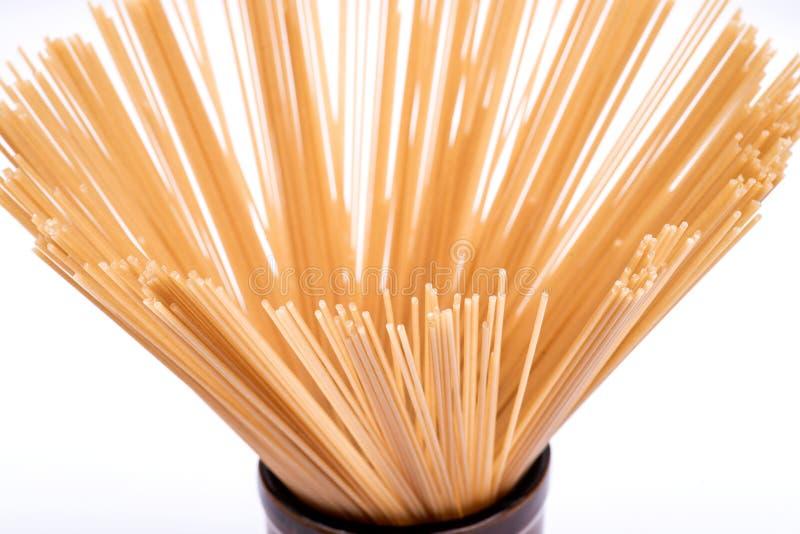 De organische ongekookte deegwaren van de Ongepelde rijstspaghetti schikten in een lange ronde bruine ceramische die kruik op wit stock foto