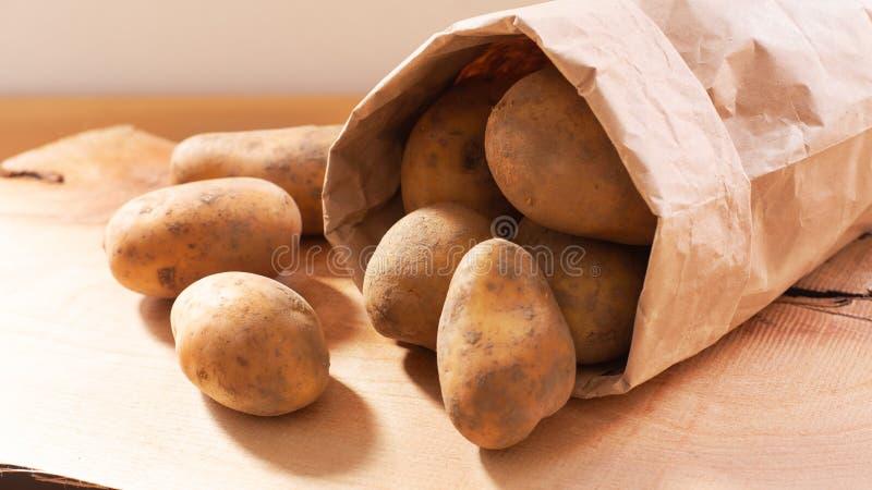 De organische verse aardappels van het natuurvoedingconcept in document zak op houten raad stock foto