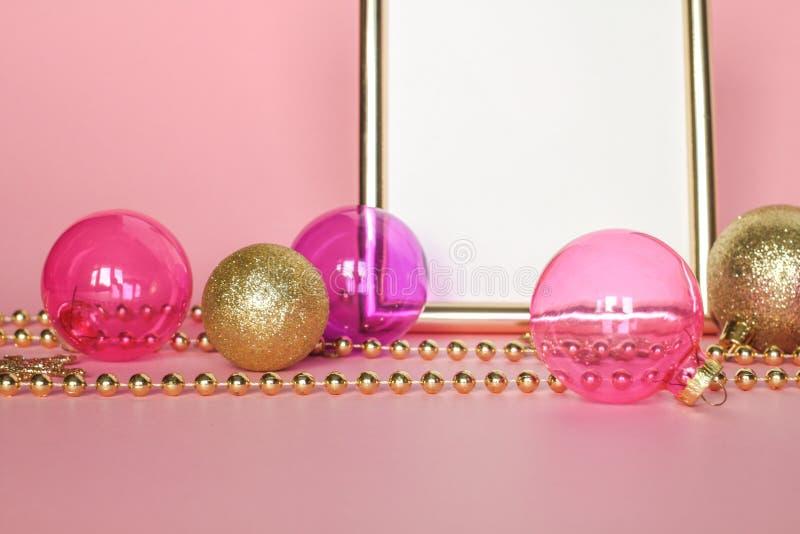 De ornamenten van manierkerstmis op roze Gouden omlijsting als achtergrond met glasdecoratie, snuisterijen, parelt stock afbeeldingen
