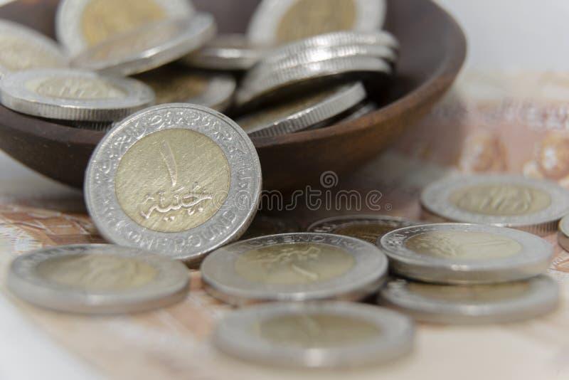 De oro y platee las monedas de 1 metal de la libra egipcia con la nuevos impresión del canal de Suez y fondo del billete de banco foto de archivo