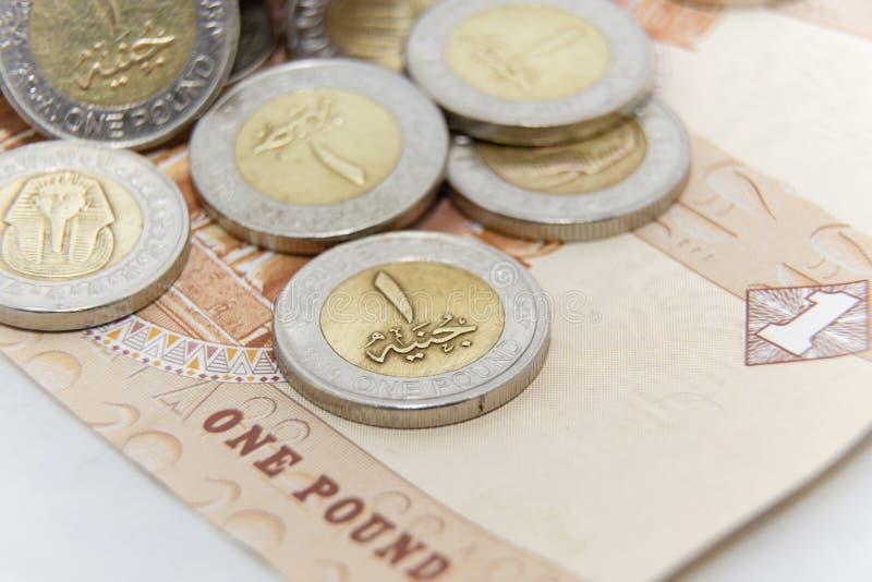 De oro y platee las monedas de 1 metal de la libra egipcia con la nuevos impresión del canal de Suez y fondo del billete de banco fotografía de archivo libre de regalías