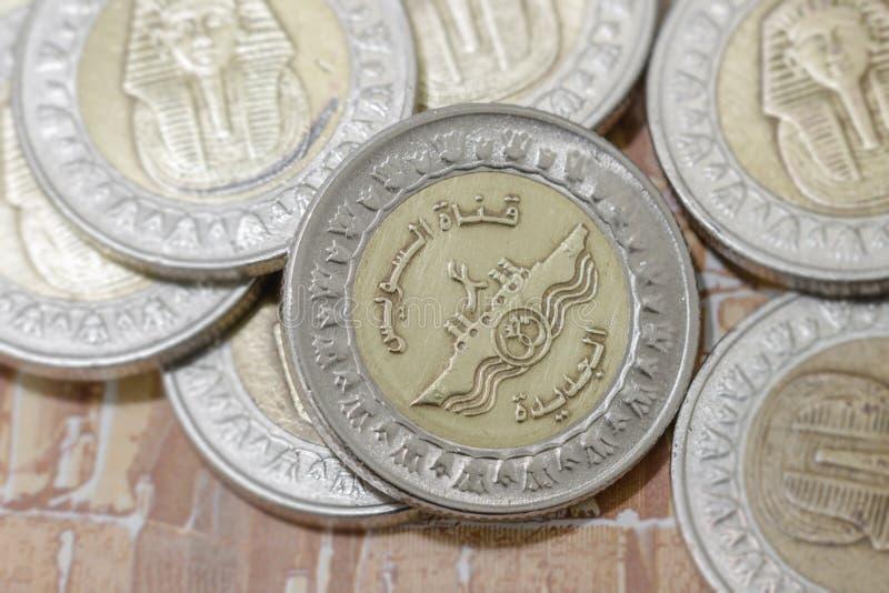 De oro y platee las monedas de 1 metal de la libra egipcia con la nuevos impresión y logotipo del canal de Suez fotografía de archivo